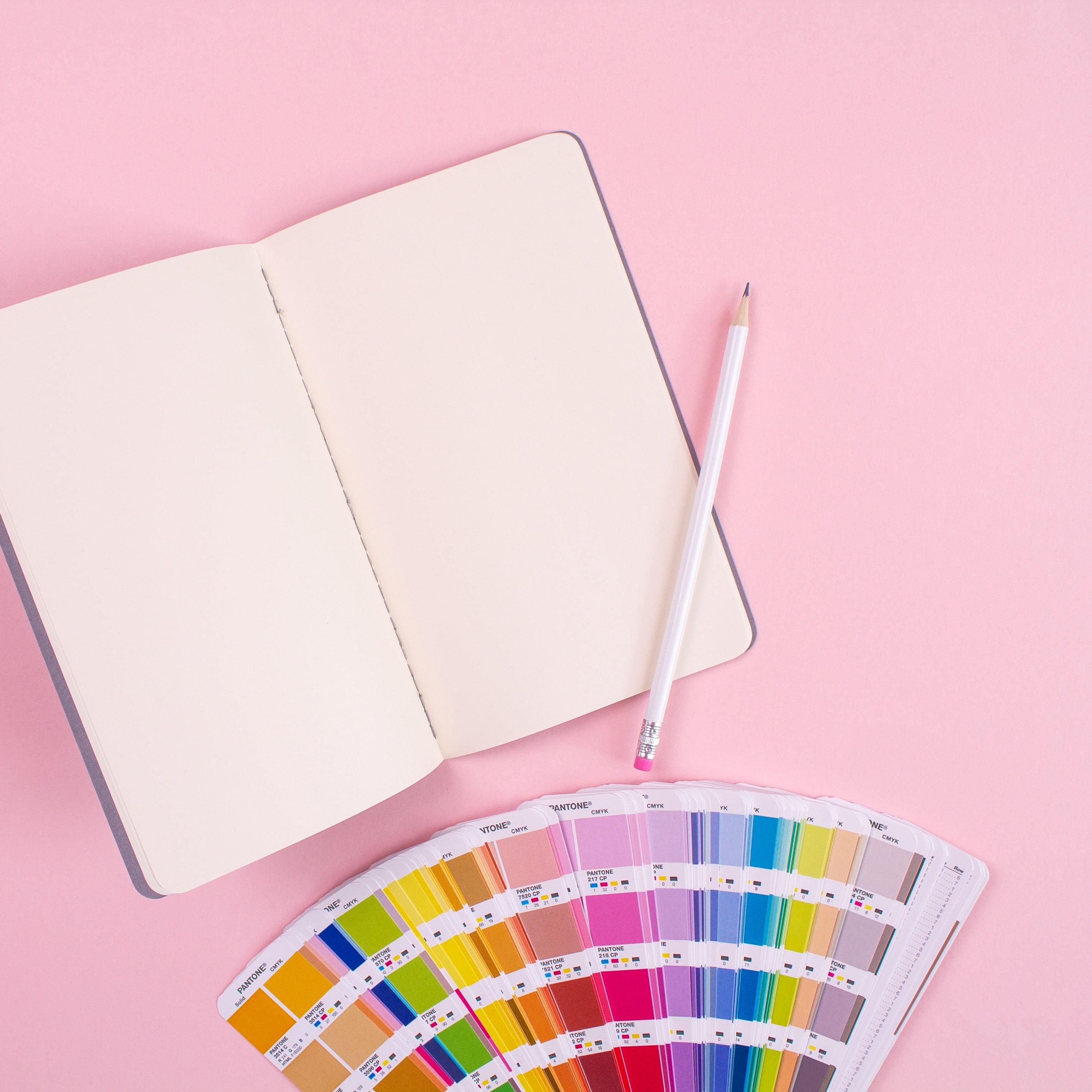 Палитра цветов и блокнот с карандашом