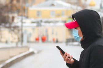 Парень в медицинской маске смотрит в экран смартфона