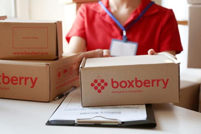 Сотрудница Boxberry с коробками