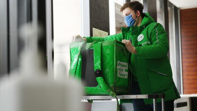 Работник Delivery Club застегивает сумку