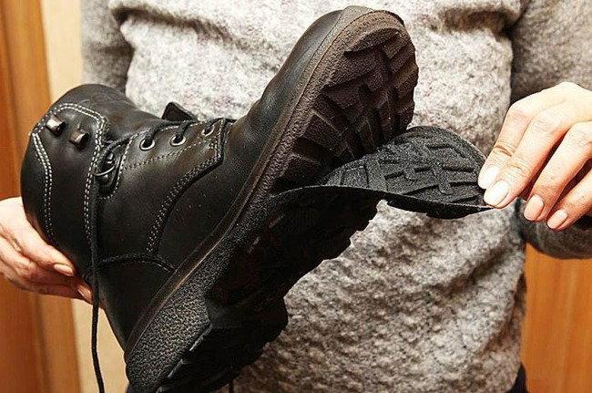 Ботинок с отходящей подошвой в руках у человека